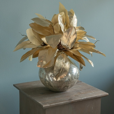 <p>Silver-gold mercury glass vase filled with golden artificial magnolia leaves. <br>For a classic and elegant setting.<br> H= about 20 cm<br> D= about 20 cm</p> - Floralia